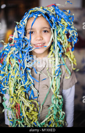 Kind kleines Mädchen mit Luftschlangen um den Hals und Kopf für die Faschingsfeier in seinem Haus - Stockfoto