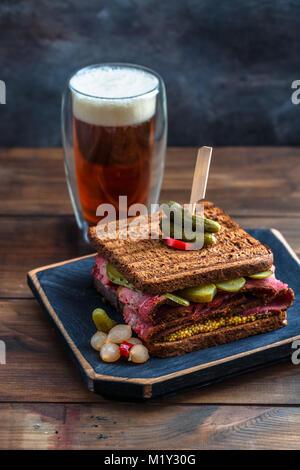 Köstliche riesige Pastrami Sandwich mit Bier und Essiggurke - Stockfoto