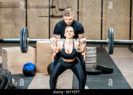 Frau Anheben ein burbell mit Trainer im Fitnessraum - Stockfoto