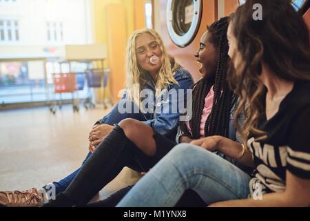 Gruppe junger Freunde sitzen auf einem Waschsalon, zusammen lachen und Seifenblasen mit Kaugummi - Stockfoto