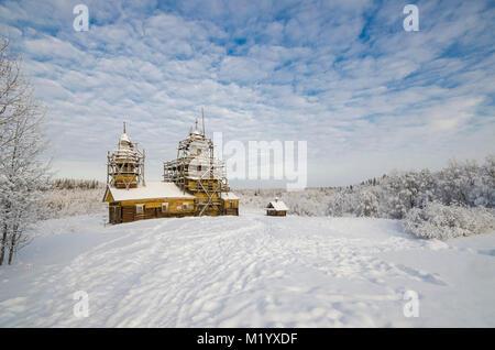 Eine hölzerne Kirche am Rande eines verschneiten Wald. Russland, Region Archangelsk, Bezirk Primorski, Kurtyevo - Stockfoto