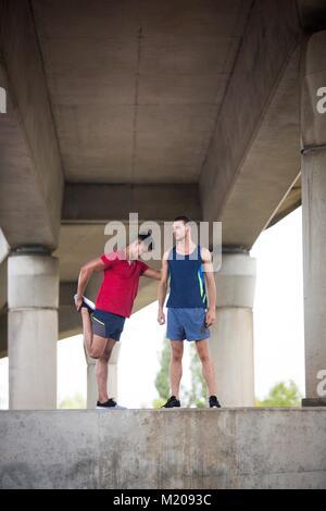 Zwei männliche Athleten stretching unter Beton Brücke. - Stockfoto