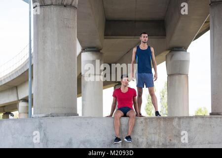 Zwei männliche Athleten unter Beton Brücke. - Stockfoto