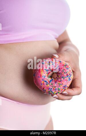 MODEL RELEASED. Frau mit Donut vor dem Bauch. - Stockfoto