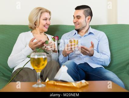 Lächelnd erwachsener Sohn gratulieren Happy ältere Mutter und schlägt einen Toast - Stockfoto