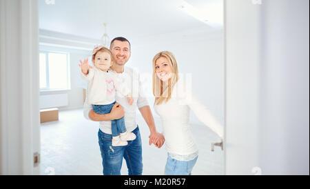 Eine glückliche Familie, öffnet die Tür zu ihrer Wohnung. - Stockfoto
