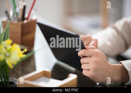 Nahaufnahme der Kaufmann Hand Digital Tablet über das Büro Schreibtisch - Stockfoto