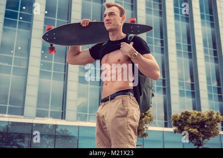Männliche mit Longboard seinen muskulösen Bauch zeigt. - Stockfoto