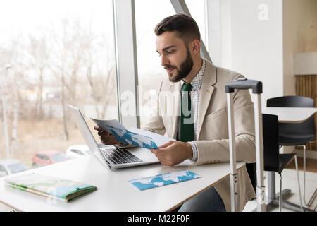 Portrait von Stattlichen bärtiger Mann Kontrolle Flugtickets am Tisch sitzen gegen Fenster im Flughafen, kopieren - Stockfoto