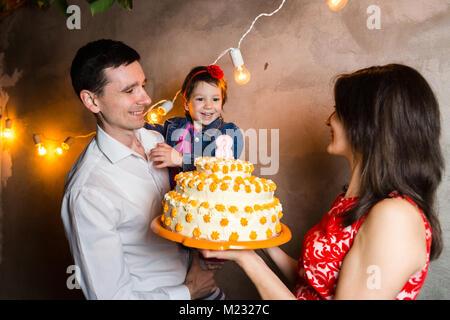 Thema Familienurlaub Kinder geburtstag und Ausblasen Kerzen am großen Kuchen. junge Familie von drei Leute stehen - Stockfoto