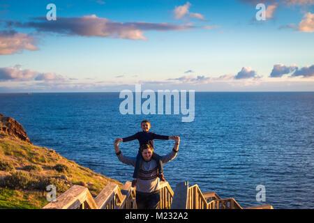 Vater seinen Sohn piggyback Ride an Hallett Cove boarwalk und genießen Sie den Sonnenuntergang, South Australia - Stockfoto