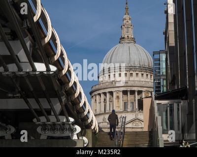 Ein Mann geht einige Schritte durch die Millennium Bridge, die zu St. Paul's Cathedral - Stockfoto