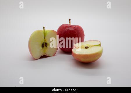Zwei Jazz Apple mit einem in der Hälfte auf weißem Hintergrund in Scheiben geschnitten - Stockfoto