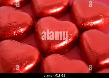 Schokolade in Herzform Herzen in rot Folie eingewickelt, close-up - Stockfoto
