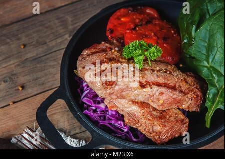 Steak selten mit dem Blut von Gemüse Tomaten und Spinat in einer Pfanne zu Hause auf dem hölzernen Tisch gegrillt. - Stockfoto