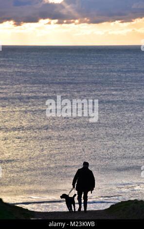 Ein Mann seinen Hund ein Weg oder Pfad hinunter zum Strand bei Sonnenuntergang in Silhouette gegen den schönen Farben - Stockfoto