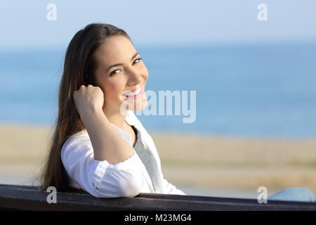 Porträt einer Schönheit Frau an der Kamera sitzt lächelnd auf einer Bank am Strand - Stockfoto