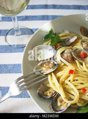Spaghetti mit Venusmuscheln, Pasta mit Meeresfrüchten auf einer Tischdecke und Glas Weißwein - Stockfoto