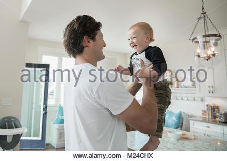 Vater holding Happy Baby Sohn in der Küche - Stockfoto