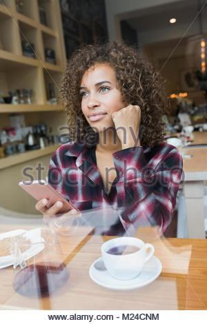 Nachdenkliche junge Frau sms mit Smart Phone und trinken Kaffee im Cafe - Stockfoto