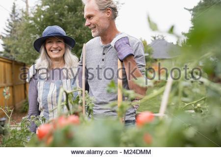 Älteres paar Gartenarbeit lächelnd - Stockfoto