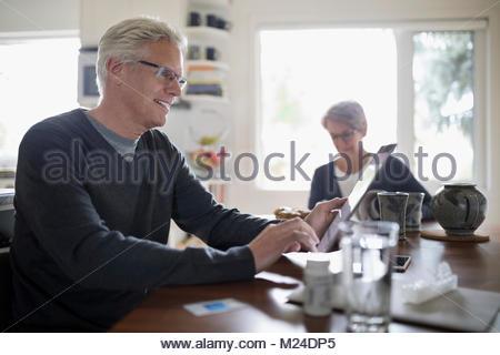 Ältere Menschen mit digitalen Tablet am Küchentisch - Stockfoto