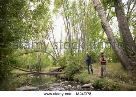 Ältere Männer Freunde mit Angelrute Fischen in Bach im Wald - Stockfoto