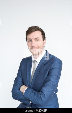 Porträt einer elegant gekleideten Mann lächelnd in die Kamera schaut. auf weißem Hintergrund - Stockfoto