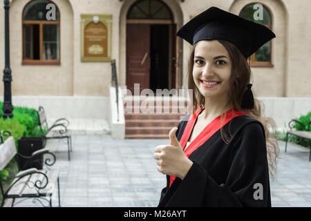 Frau Porträt auf ihrer Abschlussfeier. Daumen hoch. Universität. Bildung, Graduierung und Personen Konzept. - Stockfoto