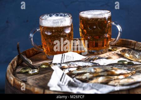 Bierkrüge mit getrockneten Fische auf einem holzschaft, dunkle Foto - Stockfoto