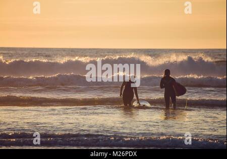 Wellenreiten an der Baskischen Küste in Anglet, an einem Abend vor Sonnenuntergang. Zwei junge Frauen aus hinter - Stockfoto