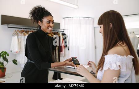 Kunden shopping Designer Verschleiß an eine Modeboutique. Kunden die Zahlung mit einer Kreditkarte auf einem Point - Stockfoto