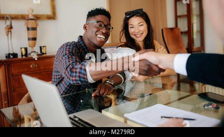 Glückliche Eigentümer Händeschütteln mit Immobilienmakler nach einem Deal. Junges Paar handshaking real estate agent - Stockfoto