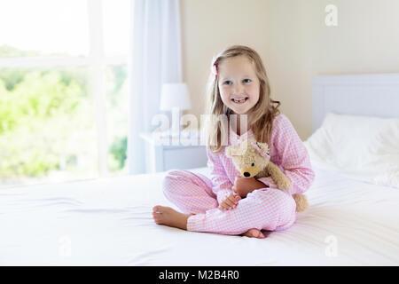 Kinder im Bett der Eltern. Kinder Aufwachen im sonnigen weißen Schlafzimmer. Kleine Mädchen in rosa Schlafanzug. - Stockfoto