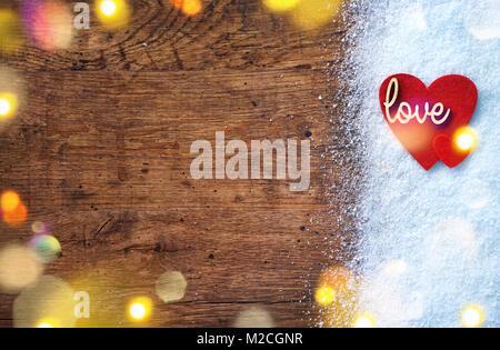 Filz rote Herzen und Holz- Inschrift 'Liebe' auf Schnee und im Hintergrund. Liebe und St. Valentines Tag Konzept. - Stockfoto