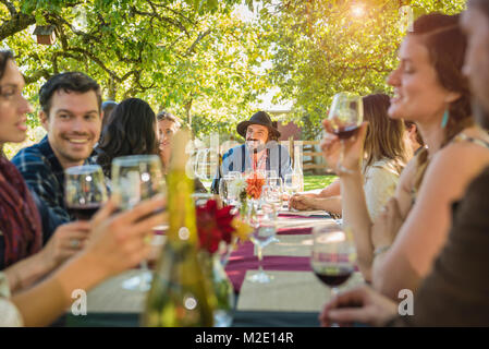 Freunde trinken Wein auf einer Party im Freien