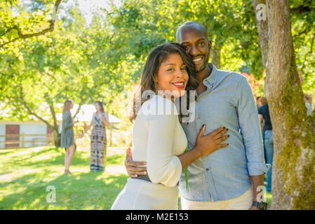 Portrait von lächelnden Afrikanische amerikanische Paar umarmen im Freien - Stockfoto