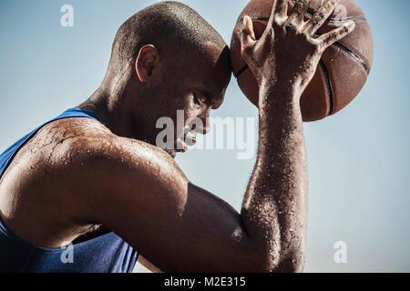 Portrait von Schwitzen Schwarzer Mann berühren Stirn mit Basketball - Stockfoto