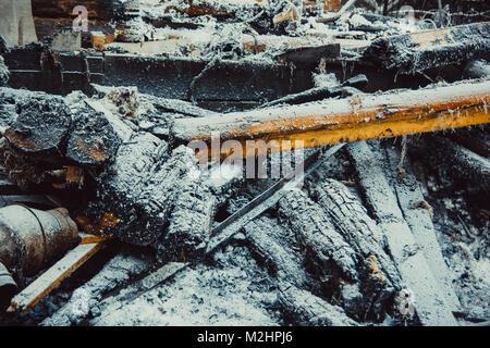 Verkohlte Glut, bedeckt mit Raureif liegen auf dem Schnee - Stockfoto