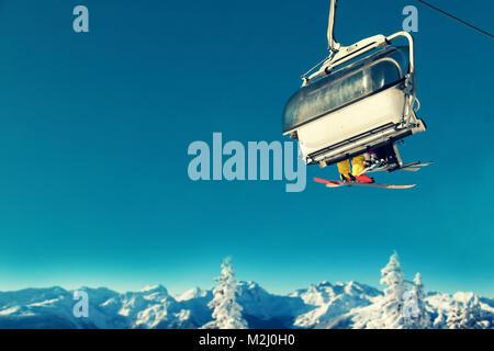 Menschen in Sesselbahn am Skigebiet über schneebedeckte Bäume und Berge