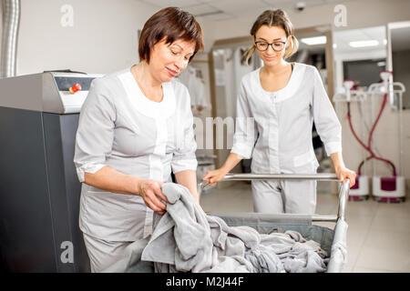 Senior washwoman mit Assistant in der Wäscherei - Stockfoto