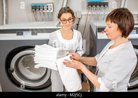 Senior washwoman mit jungen Assistenten in der Wäscherei - Stockfoto