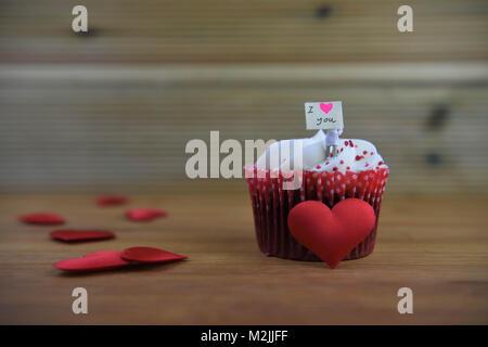 Romantischer Valentinstag Cupcake mit einer Miniatur person Figur hält ein Schild und Rote Liebe Herz Formen dekoriert - Stockfoto