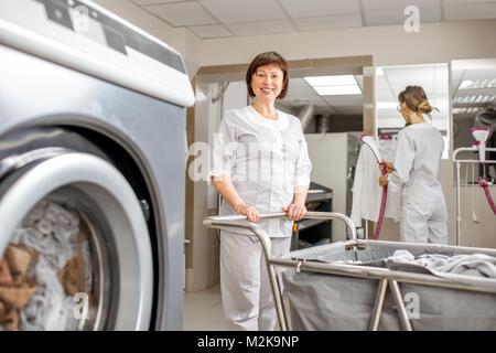 Senior washwoman in der Wäscherei arbeiten - Stockfoto