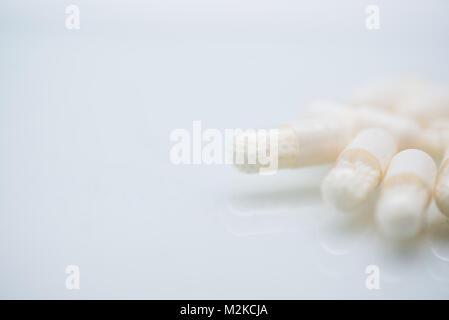 Nahaufnahme von weiße Kapsel Pillen, Arzneimittel, Medizin, Medikamente oder Vitaminpräparate. Monochromatische - Stockfoto