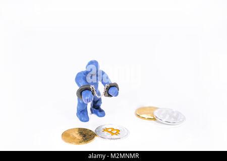 Kleine blaue Figur in Handschellen. Aus dem Spiel Ton gemacht. Auf weissem Hintergrund.