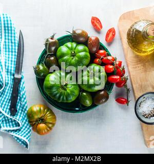 Verschiedene Arten, Typen und Farbe von Tomaten auf einem weißen Tisch aus Stein. Zutaten für eine gesunde Ernährung: - Stockfoto