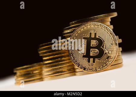 Aus der Nähe Golden bitcoin vor einem Stapel von Golden metallische Münzen auf schwarzen dunklen Hintergrund - Stockfoto