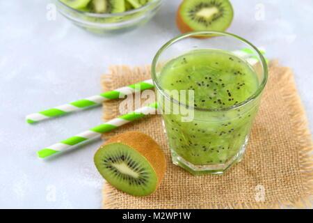Kiwi in Scheiben geschnitten und Smoothie Schichten in einem Glas auf einem grauen Tabelle. Gesunde Ernährung - Stockfoto