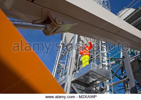 Ingenieur tragen Hi viz Schutzkleidung auf Stahl Plattform von Zement Verarbeitungsbetrieb - Stockfoto